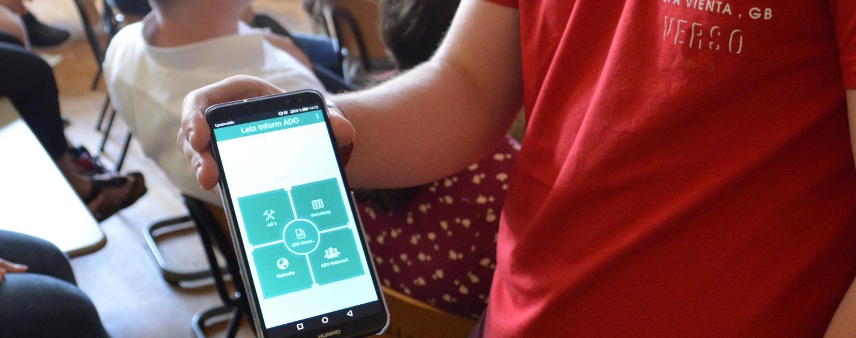 Ein Schüler zeigt ein Smartphone, auf dem er einen Prototyp einer Schul-App entwickelt hat.