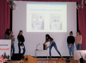 Eine Gruppe Schülerinnen präsentiert auf der Bühne ihr Projekt.