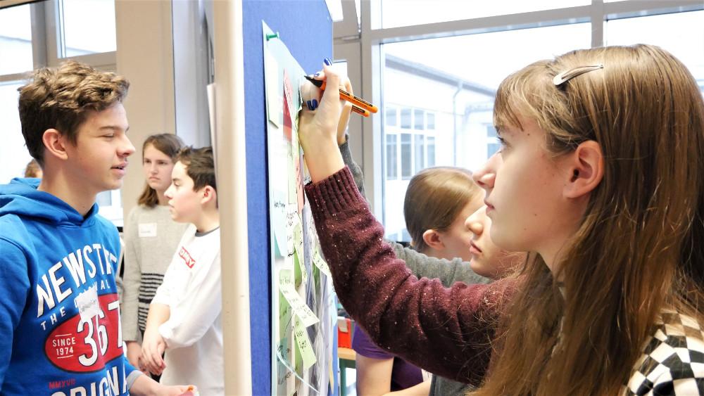 Schülerinnen und Schüler beschreiben Plakate auf einer Stellwand