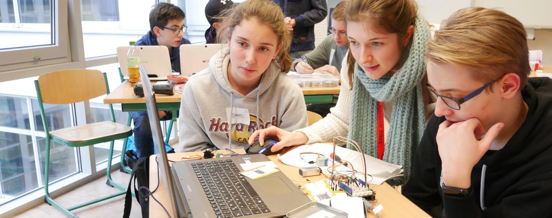 Eine Mentorin hilft einem Schüler und einer Schülerin beim Programmieren.