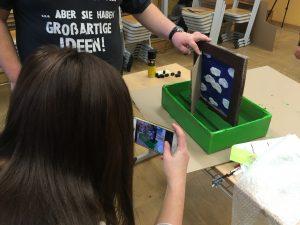 Eine Schülerin fotografiert mit ihrem Handy das Modell eines Fensters.