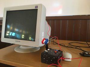 Eine selbstgebaute schwarze Kiste ist an einem Bildschirm angeschlossen.