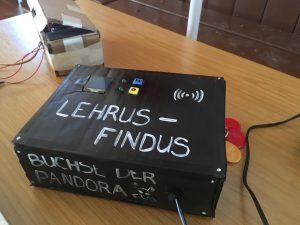 """Auf einer schwarz angemalten Kiste steht """"Lehrer-Findus""""."""