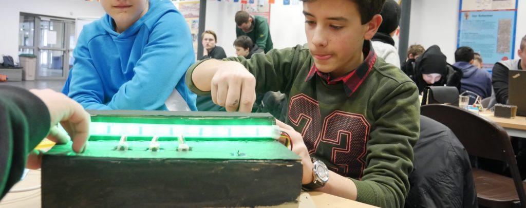 Schüler basteln an einem Modell aus Pappe. Auf der Pappkiste ist ein grün leuchtender LED-Streifen befestigt.