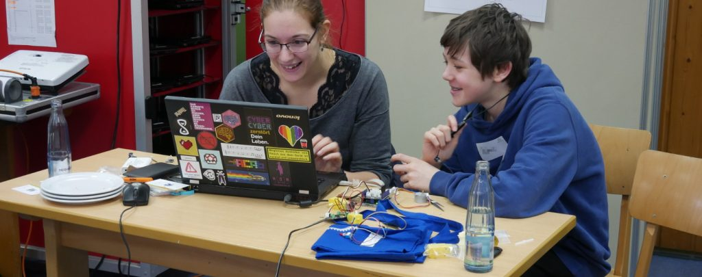 Eine Mentorin sitzt vor einem mit vielen bunten Aufklebern beklebten Laptop. Sie lacht. Neben ihr ein Schüler, der mit ihr auf den Bildschirm des Laptops schaut, er lacht ebenfalls.