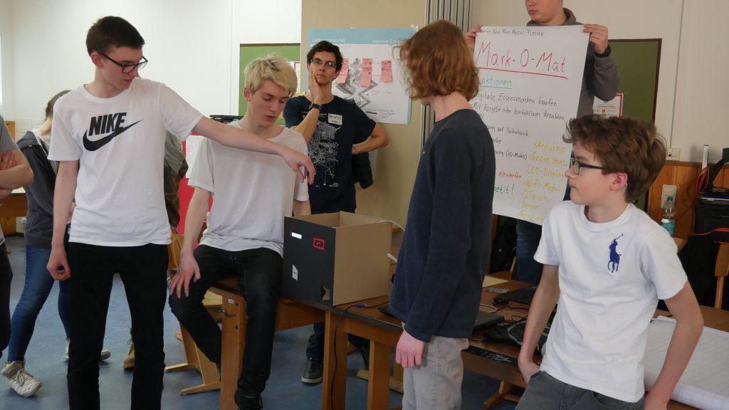 Eine Gruppe Schüler steht um einen selbstgebauten Pappkasten herum und zeigt die Funktionen des Prototyps.