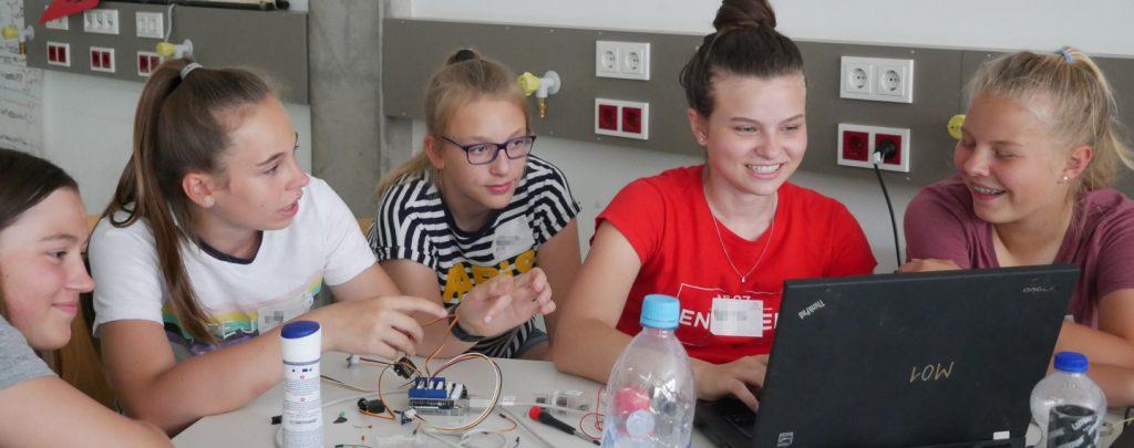 Fünf Mädchen sitzen um einen Laptop und schauen lachend auf den Bildschirm. Auf den Tischen vor ihnen liegen allerlei Kabel und elektronische Bauteile.