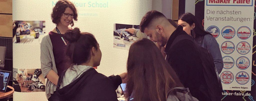 Eine Gruppe von Menschen schaut sich interessiert den Messestand von Make Your School an.