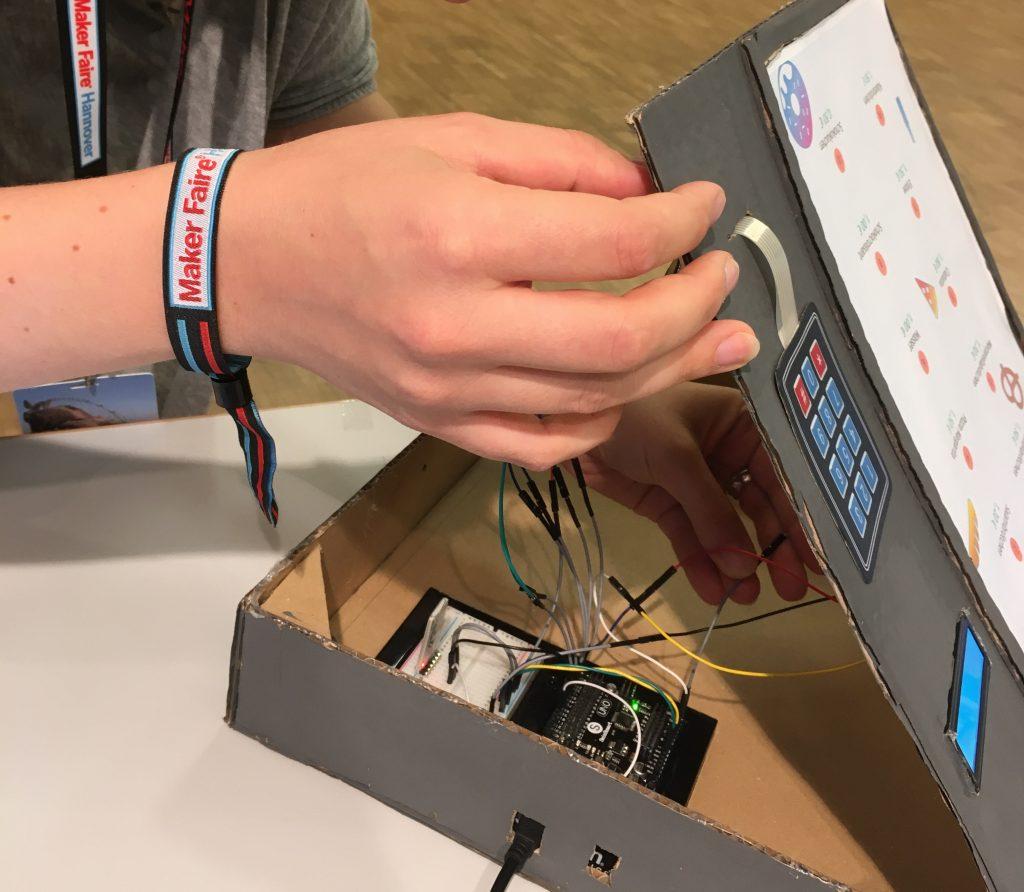Eine Hand öffnet einen selbstgebauten Prototypen. Im Inneren offenbaren sich viele Kabel und ein Mikrocontroller.