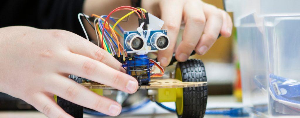 Kinderhände verbinden Kabel an einem kleinen Roboter.