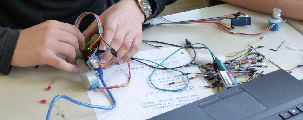 Hände verbinden Kabel mit einem kleinen Motor.