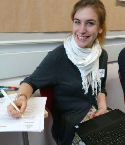 Francine Meyer sitzt an einem Tisch und füllt Dokumente auf.