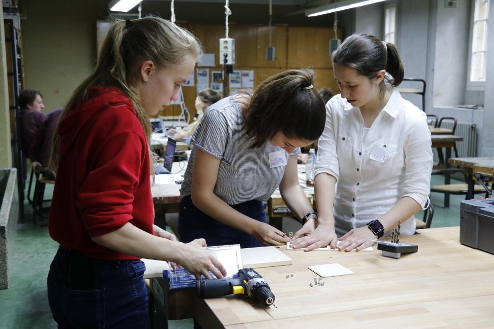 Drei Mädchen arbeiten mit Holz und Bohrmaschine.
