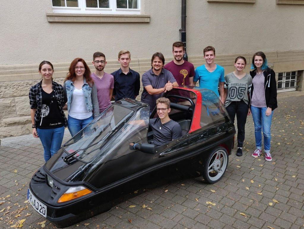 Ein Lehrer inmitten seiner Schülerinnen und Schüler. Ein Schüler sitzt im selbstgebauten Elektroauto.