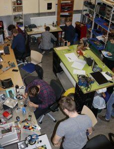 Ein Blick von oben in einen Werkraum, in dem Jugendliche konzentriert tüfteln und basteln.
