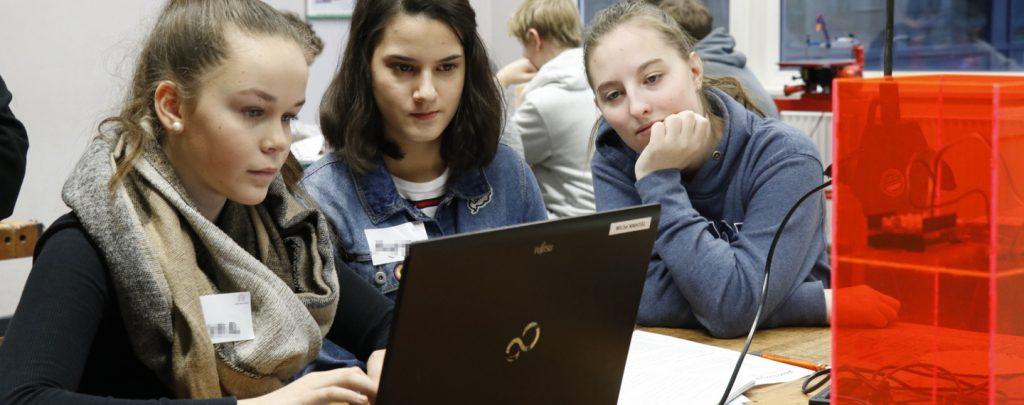 Drei Mädchen sitzen konzentriert vor einem Laptop.