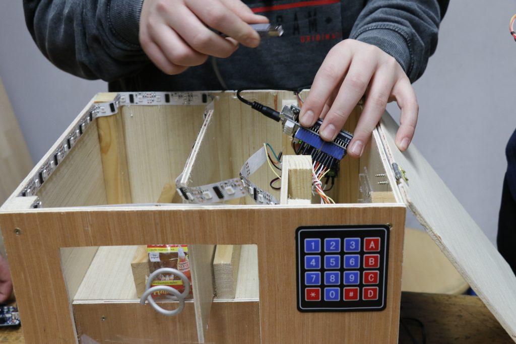 Eine Hand setzt einen Mikrocontroller mit Kabeln in eine Holzkiste.