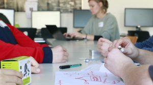 Schüler sitzen um ein Plakat mit Planzeichnungen darauf.