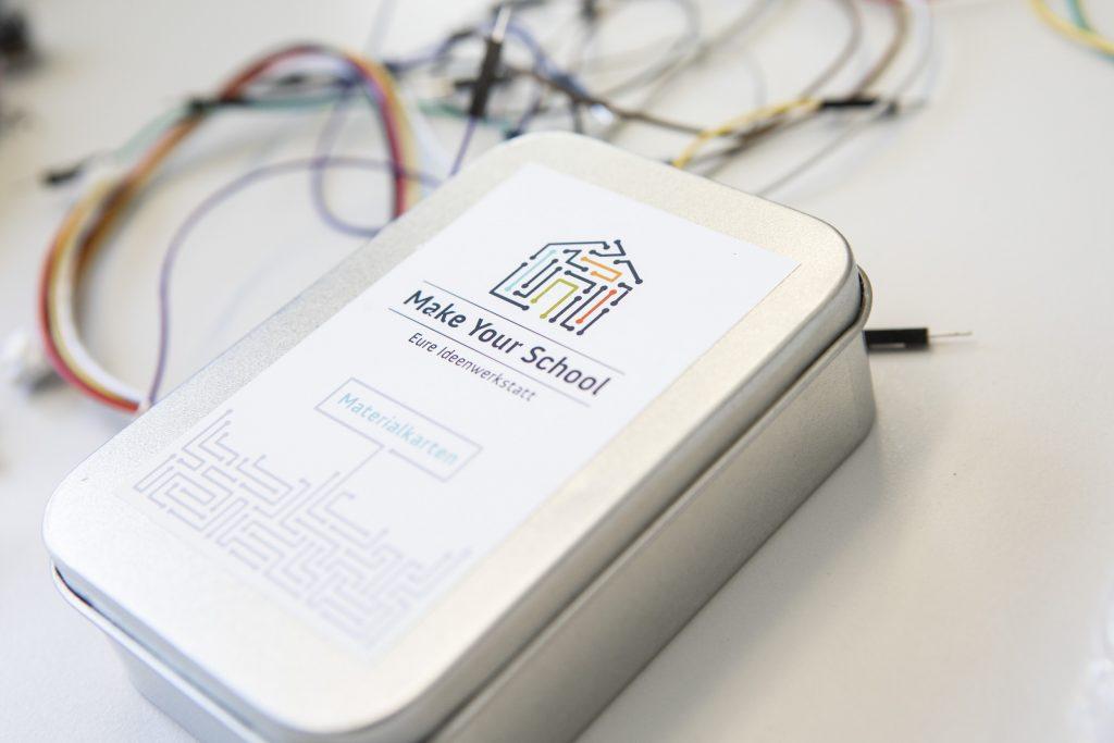"""Man sieht eine silberne kleine Alubox. Darauf ist das Logo von Make Your School zu sehen und die Worte """"Materialkarten"""""""