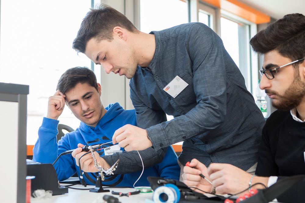 Ein junger Mann zeigt zwei Schülern wie man den Lötkolben bedient.