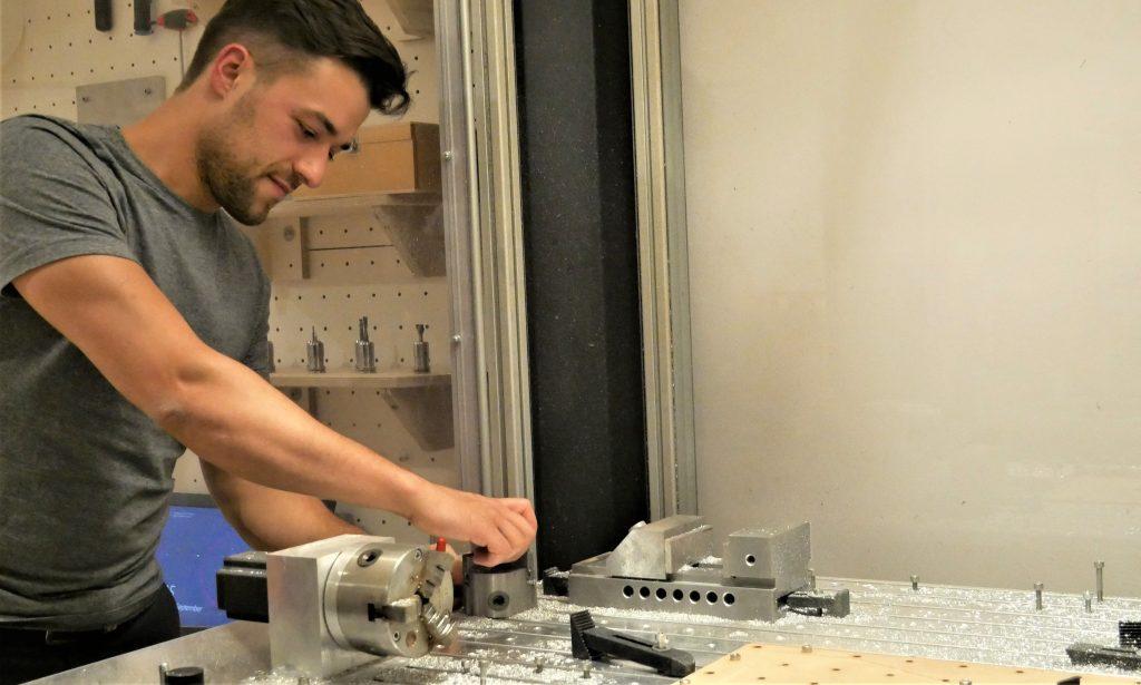 Ein junger Mann bedient konzentriert eine Maschine. Sie sieht aus die eine metallene Werkbank.