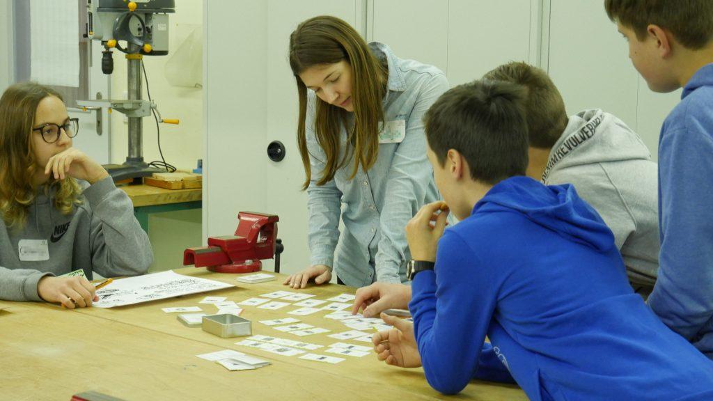 Eine junge Frau beugt sich über Schüler und schaut ihnen über die Schulte wie sie Karten mit technischen Bauteilen darauf begutachten.