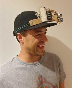 Ein Mann trägt eine Kappe auf der ein Mikrocontroller und eine Abstandssensor montiert sind.