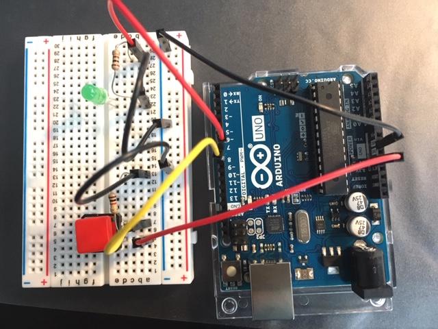 Ein Arduino Uno ist mit Kabeln an ein Breadboard angeschlossen. Darauf sind eine grüne LED und ein roter kleiner Knopf aufgesteckt.