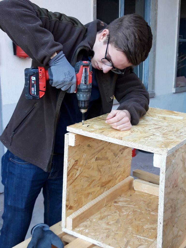 Ein Junge schraubt mit einem Akkubohrschraube eine Schraube in eine Holzgehäuse.