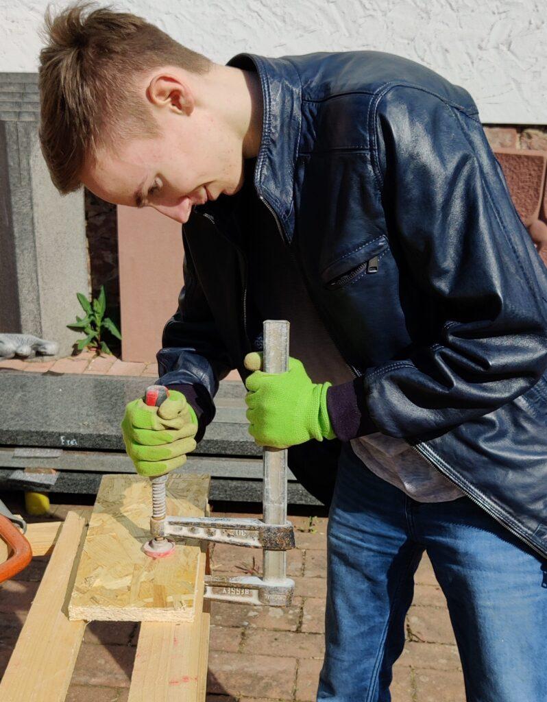 Ein Junge fixieret mit einer Schraubzwinge ein Holzstück vom Gehäuse.