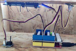 Verschiedene Kabel und ein Mikrocontroller sind in dem Holzgehäuse zu sehen. Eine grüne LED leuchtet auf.