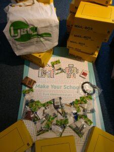 Auf dem Bild ist ein Plakat von Make Your School mit einzelnen Bestandteilen des Material-Kits zu sehen. Neben den gepackten Boxen ist ein Stoffelbeutel vom LJBW zu erkennen.